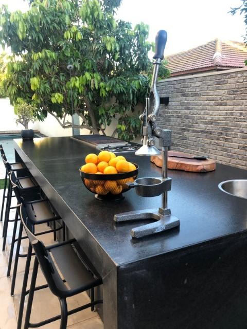 מטבח חוץ משולב בר ישיבה בחיפוי שיש גרניט. מאובזר גריל גז 9 מבערים מבית שאולי, כיור מקרר וארונות אחסון
